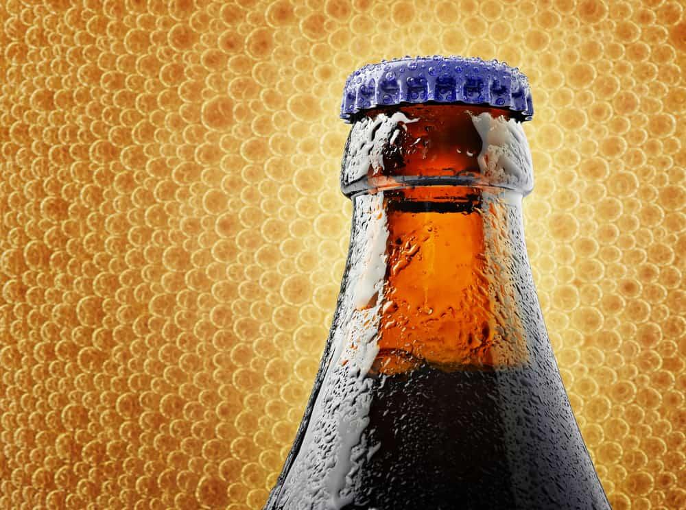 Toppen af en flaske belgisk Belgisk Chimay øl med bobler i baggrunden.