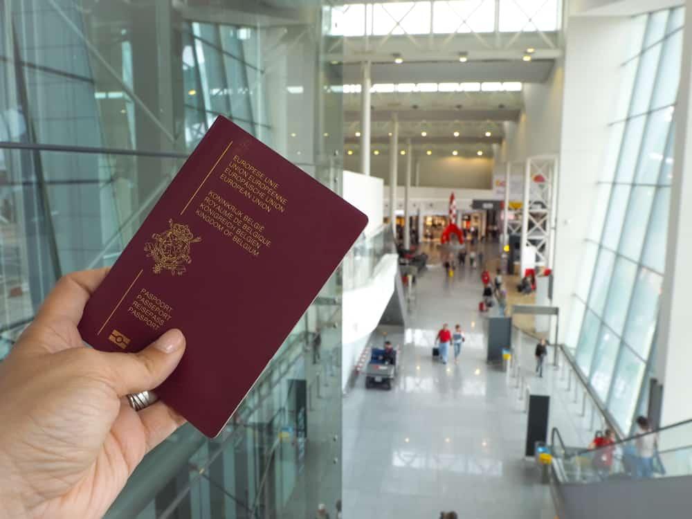I forgrunden et europæisk pas og i baggrunden view over Bruxelles Internationale Lufthavn (BRU)