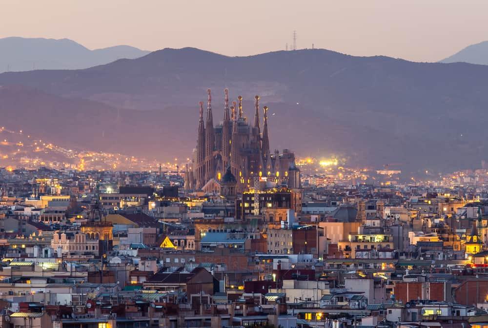 View over Barcelona-bydelen Eixample i skumringen med Sagrada Familia i baggrunden