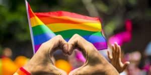 Hænder der former et hjerte og regnbueflaget til Christopher Street Day i Berlin.