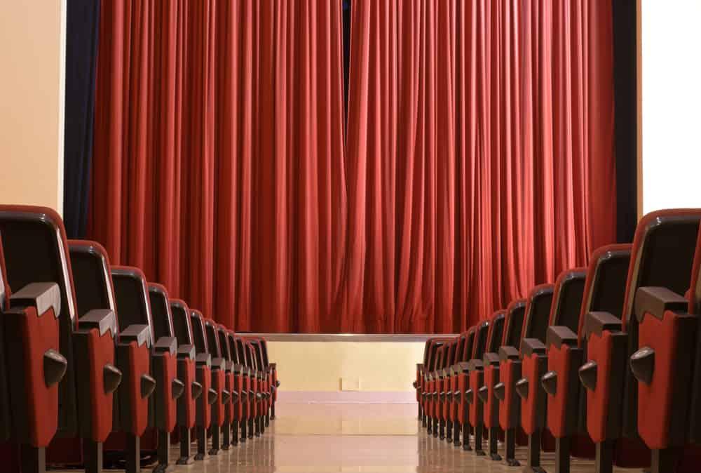 Det indvendige af en biograf. Biografsæder på begge sider af et lærred dækket til af tæppet.