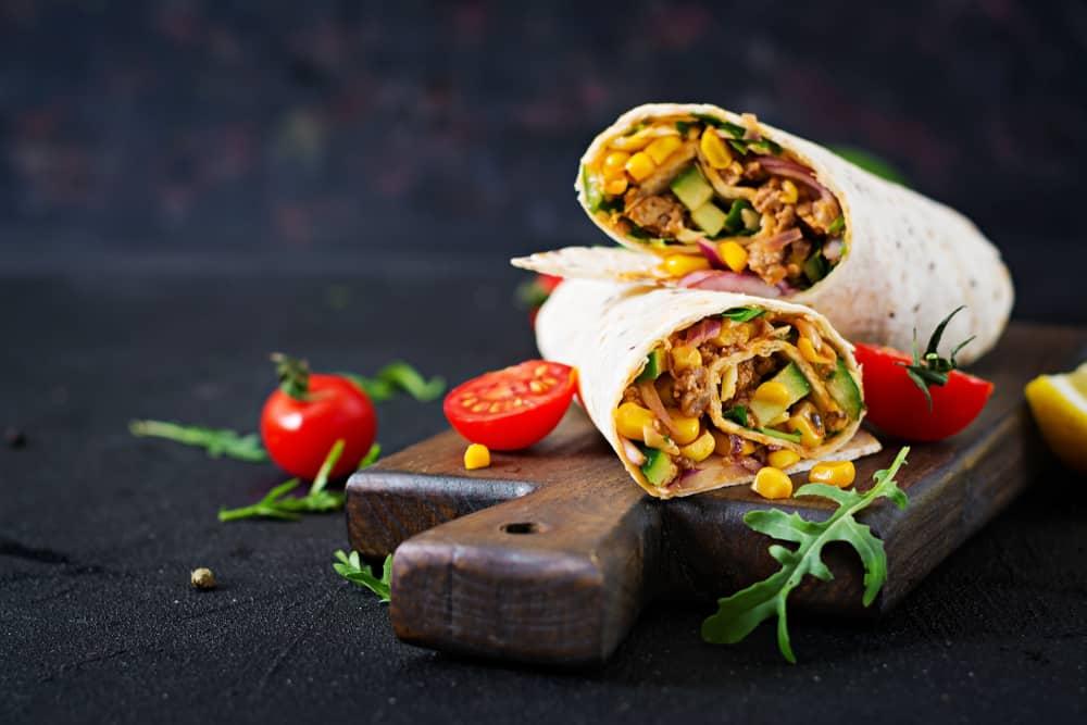 Burritoes på et skærebræt med tomater ved siden af.