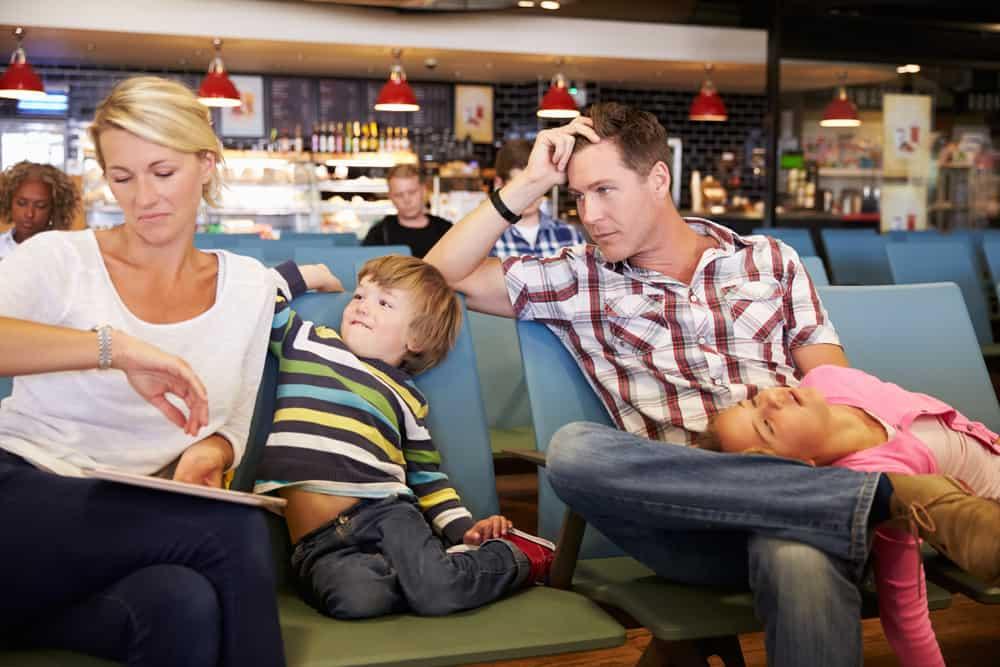Lille famile som venter på deres fly i lufthavnen.