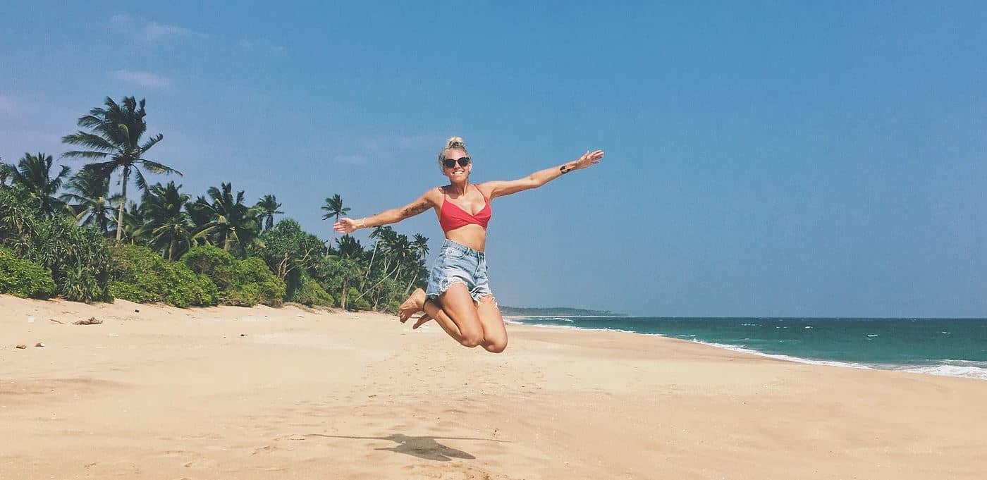 Mathilde Odgaard på Sri Lanka. Hopper på bounty strand med palmer i baggrunden og skyfri himmel.